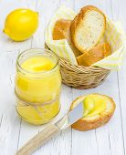 picture of curd  - Lemon curd with lightly toasted baguette on a wooden table - JPG