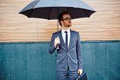 foto of entrepreneur  - Young entrepreneur with briefcase standing outside under umbrella - JPG