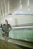 picture of escalator  - Serious businessman standing on ascending escalator - JPG