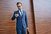 picture of sms  - Businessman with briefcase and cellphone writing or reading sms - JPG