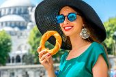 stock photo of bagel  - Young woman eating turkish bagel in Istanbul - JPG