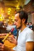 stock photo of shisha  - Man smoking turkish hookah in the cafe with coloful lamps on background in Istanbul - JPG