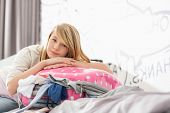 stock photo of bulge  - Portrait of girl relaxing on bulging suitcase at home - JPG