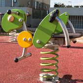 stock photo of playground  - Bouncy colorful spring playground equipment in public park plastic grasshopper on springs - JPG