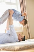stock photo of pick up  - Side view of playful father picking up son while lying on floor at home - JPG