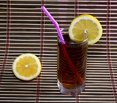 image of cold drink  - glass ofglass of cold black tea with a lemon - JPG