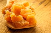 stock photo of candy  - Closeup candied crystallized ginger candy pieces on wooden spoon - JPG
