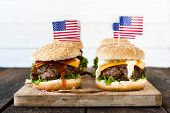 picture of beef-burger  - American mini beef burgers with cheese and USA flags on wooden boardselective focus - JPG