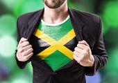 stock photo of rastafari  - Businessman stretching suit with Jamaica Flag on bokeh background - JPG
