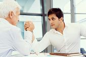 pic of wrestling  - Two businessmen competeting arm wrestling in office - JPG