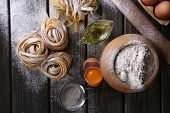 image of pasta  - Raw homemade pasta and ingredients for pasta on wooden background - JPG