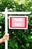 stock photo of yard sale  - Wooden Yard Sale sign in female hand over green bush and flowers background - JPG