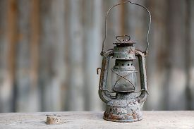 pic of kerosene lamp  - Old metallic rusty kerosene lamp with vintage background. Retro nostalgia home decoration concept.