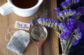 stock photo of peppermint  - peppermint tea on spoon and tea bag with tea time tag on wooden background - JPG