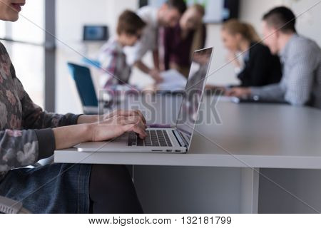 young  business woman at modern startup office interior working on laptop computer, blured team in m