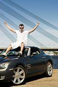 Постер, плакат: Счастливый молодого человека сидящего на вершине его современный спортивный автомобиль