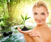 stock photo of beauty nature  - Beautiful woman with young plant in forest - JPG