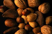 stock photo of nutter  - large mound of assorted nuts on black background - JPG