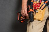 Close up of handyman holding a drill machine with tool belt around waist. Detail of artisan hand hol poster