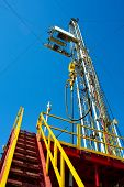 pic of oil drilling rig  - Tall land drilling rig under blue sky - JPG
