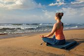 Woman doing yoga - meditating and relaxing in Padmasana Lotus Pose outdoors at tropical beach on sun poster