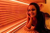 A Young Smiling Girl Lies In A Tanning Bed Under The Ultraviolet Rays, Sunbathing, Wants A Tanned Sk poster