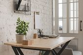 Interior Of Contemporary Workspace With Wooden Table And Flower And Organized Stationery. poster