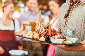 In Beer garden in Bavaria, Germany - beer and snacks are served, focus on meal poster