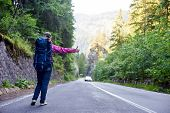 Hiker Girl With Blue Backpack With Hand Thumb Up Hitchhiking By The Side Of The Road. Young Traveler poster