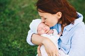 Loving Mother With Her Newborn Baby On Her Arms. poster