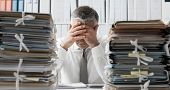 Stressed Business Executive And Piles Of Paperwork poster