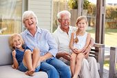 Grandparents With Grandchildren Relaxing On Deck At Home poster