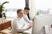 Постер, плакат: Two Caucasian Designers Working In Modern Office Using Generic Computer: Stylish Mature Female Shari