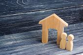 Figurine Wooden House With Two People Side By Side On A Background Of Black Boards. Concept Of Real  poster