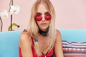 People, Style And Lifestyle Concept. Blonde Serious Female Wears Red Sunglasses, Sits On Comfortable poster