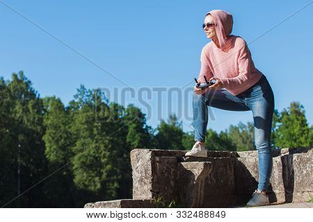 poster of Young Woman Wearing Sunglasses And Hoodie Holding A Remote Control, Controls, Controls Are Not Visib