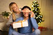 Cheerful Woman Having Christmas Surprise For Husband, Closing His Eyes From Back poster
