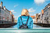 Woman Tourist Sits With His Back To The Camera And Enjoy The View Of The Canal In The Historical And poster