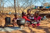 two african children in a village near Kalahari desert, the sister feeding her brother in the outdoo poster