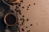 Brown Coffee Cup With Coffee Beans And Brown Napkin On Brown Textured Background. Top View. Copy Spa poster