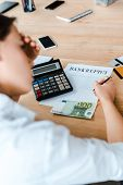 Selective Focus Of Woman Signing Document With Bankruptcy Letters Near Credit Cards And Euro Banknot poster