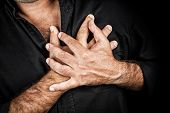 stock photo of medical condition  - Close up of two hands grabbing a chest on a black background - JPG