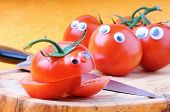 foto of googly-eyes  - Funny tomatoes with googly eyes on cutting board