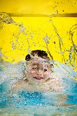 Young boy or kid has fun splashing into pool after going down water slide during summer with copy sp