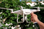 Man Is Holding A Drone In Hand And Using Of New Technology. White Quad Copter Drone And Photographer poster