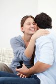 stock photo of jewel-case  - Couple embracing each other while holding a jewel case against grey background - JPG