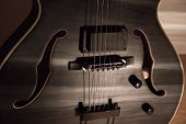 Black Jazz Archtop Guitar With Holes. Hollow Steel-stringed Acoustic Or Semiacoustic poster