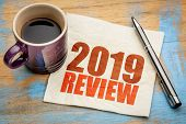 2019 year review text on a napkin with a cup of coffee, end of year business concept poster