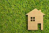 Little Wooden Miniature House Model On Green Grass Background With Copy Space - Ecological Living Or poster