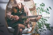 Beautiful Woman Playing Guitar In Swing Chair. Woman Relaxing In Swing Chair At Home. Hipster Lifest poster